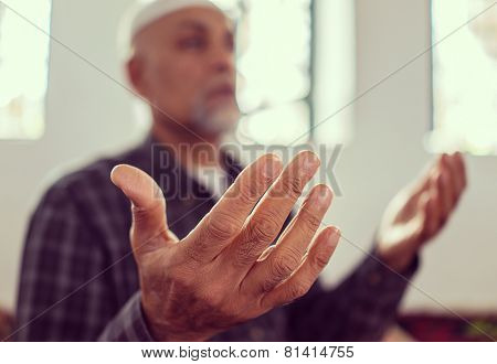 Senior Arabic Pakistani man praying in mosque