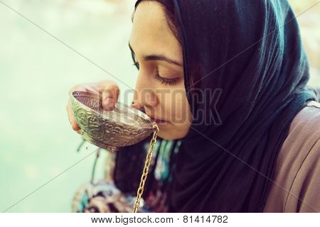 Arabic Muslim Middle Eastern girl drinking clean water on the river spring