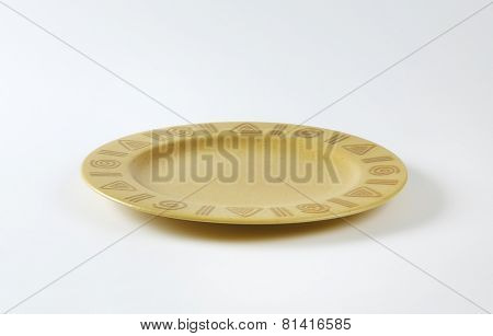 Rustic ceramic plate decorated with symbols on the rim