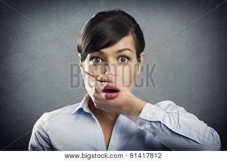 Shocked businesswoman with mouth open, isolated on grey background.