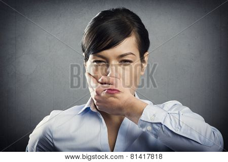Angry upset businesswoman with hand covering her mouth, isolated on grey background.