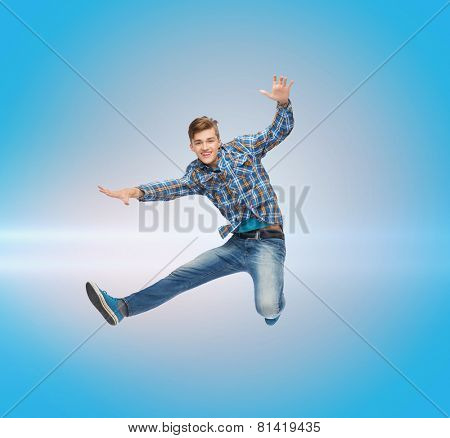 happiness, freedom, movement and people concept - smiling young man jumping in air over blue laser background