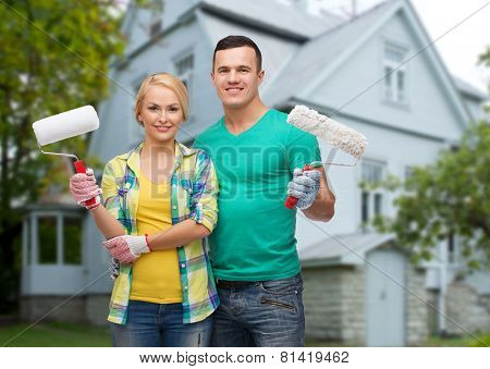 repair, people, real estate, home and family concept - smiling couple with paint rollers over house background