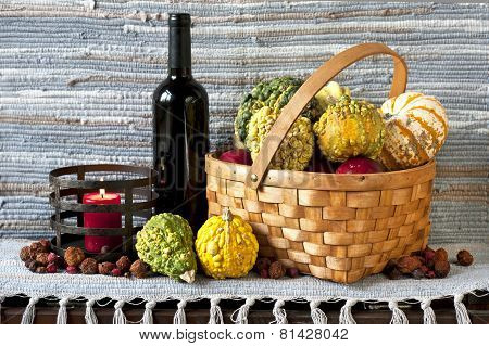 Pumpkins In Basket With Bottle Of Red Wine And Candle On Texture Background