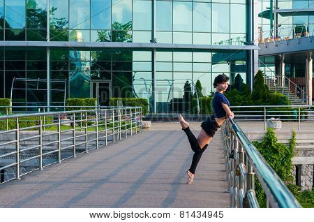 Ballet dancer in casual clothes standing on tiptoes operands hands on railing