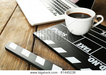 Movie clapper with laptop and cup of coffee on wooden background