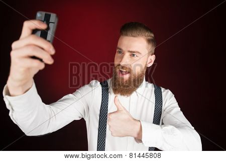 Cheerful young man with beard making selfie