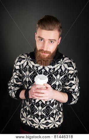 Young man with beard holding a cup of coffee