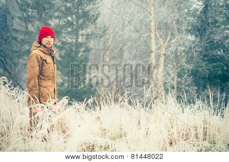 Young Man wearing winter hat clothing outdoor with foggy forest nature on background