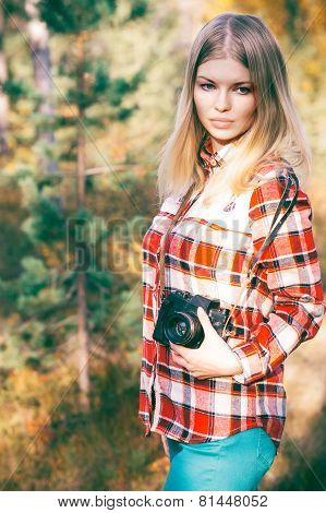 Young Woman walking with retro photo camera outdoor