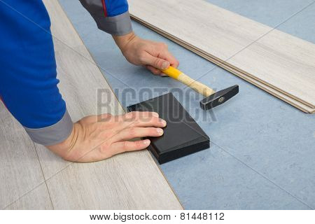 Close-up Of A Worker Assembling Laminate Floor