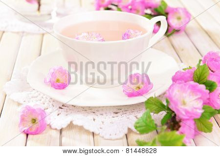 Beautiful fruit blossom with cup of tea on table on light background