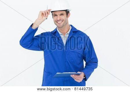 Portrait of happy supervisor wearing hard hat while holding clip board over white background