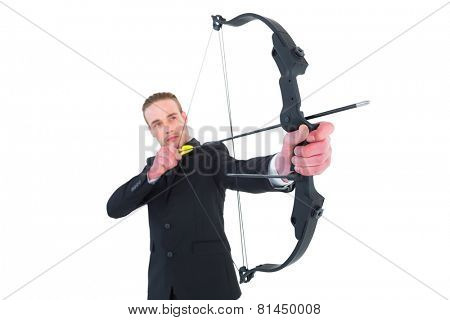 Concentrated businessman shooting a bow and arrow on white background