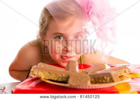 Hungry gesture blond kid girl in party with chocolates at birthday