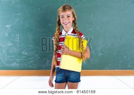 Blond braids schoolgirl with student spiral notebook at class green chalk board