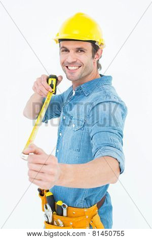 Portrait of happy male architect holding tape measure over white background