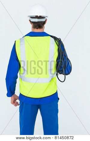 Rear view of electrician with wire standing against white background