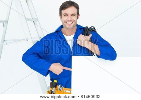 Portrait of handsome electrician with wire pointing at bill board over white background