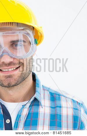 Portrait of confident repairman wearing protective glasses and hard hat on white background