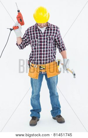 Full length of male repairman holding drill machine and hammer on white background