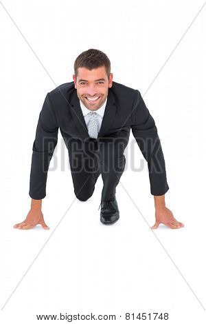 Smiling businessman crouching on white background