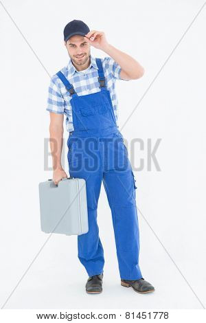 Full length portrait of confident male repairman carrying toolbox on white background