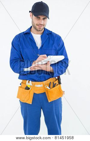 Portrait of repairman writing on document while standing against white background