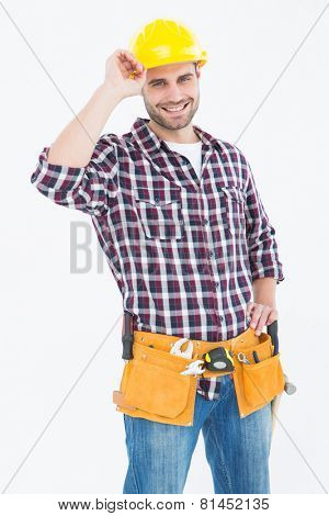 Portrait of confident handyman wearing hard hat on white background