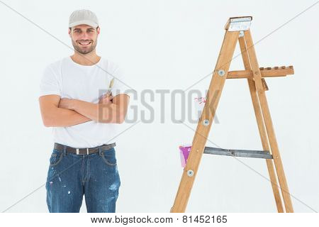 Portrait of happy man holding paintbrush while standing by ladder on white background