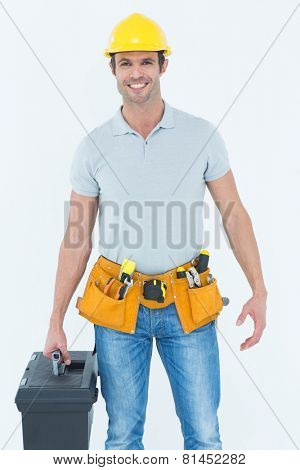 Portrait of confident technician holding tool box over white background