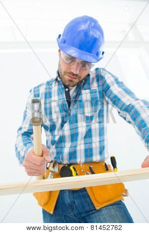 Low angle view of carpenter hitting nail on wooden plank at home