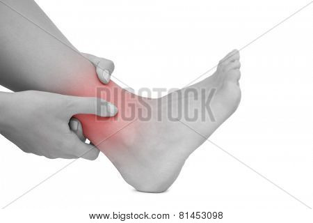 Young woman sitting on ground touching her injured foot on white background