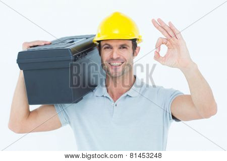 Portrait of happy worker carrying tool box on shoulder while gesturing OK sign over white background