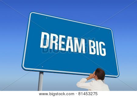 The word dream big and thinking businesswoman against bright blue sky