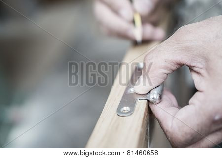 Closeup of carpenter hand with pencil working on door hinge