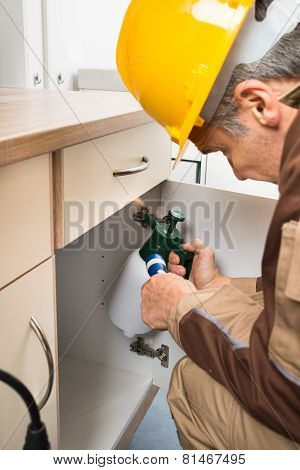 Pest Control Worker Spraying Pesticides Inside Cabinet
