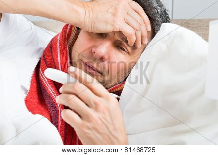 Mature Sick Man Holding A Thermometer