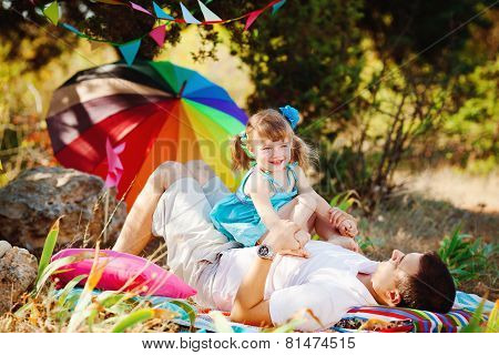 The cheerful young family has a rest in park in the summer on a grass.