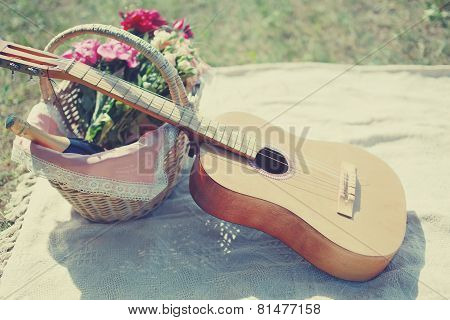 Guitar, Basket With Wine And Bouquet Of Flowers. Vintage Tender Background