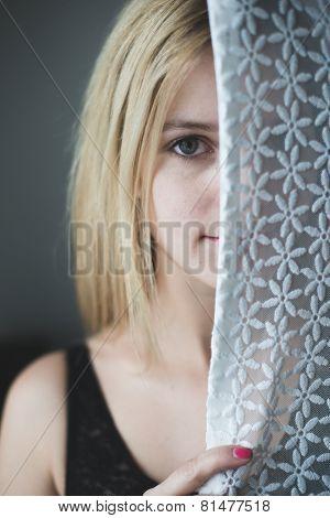blonde woman hiding behind the curtain