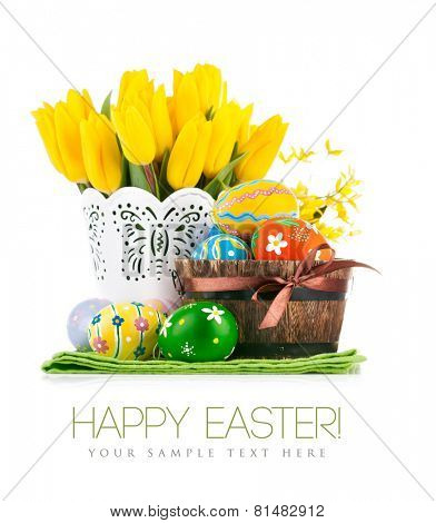 Easter eggs in basket with yellow tulips. Isolated on white background