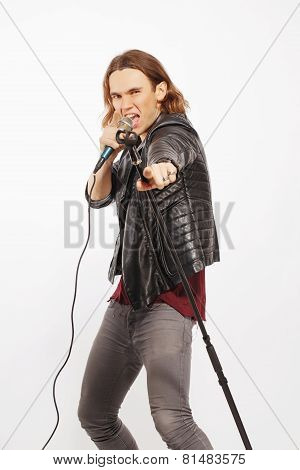 Young handsome rock singer holding microphone