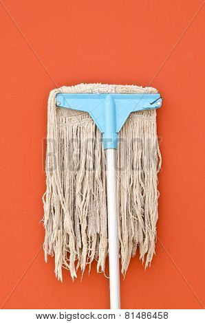 Dirty Mop Against On Brown Wall