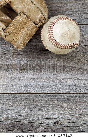 Used Baseball And Weathered Mitt On Old Wood
