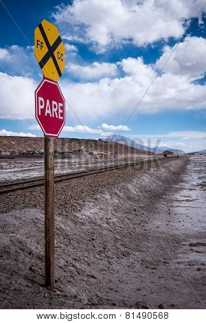 Stop Sign (pare) At Railway Crossing In A Desolate Landscape