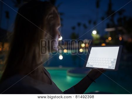 Woman tourist with pad on tropical resort in late evening