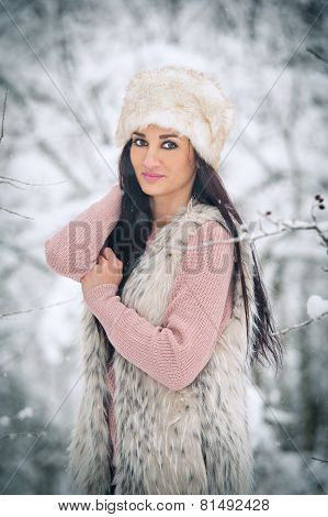 Woman with white fur cap and sheepskin  smiling enjoying the winter scenery in forest