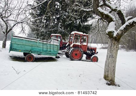 Old Small Agriculture Tractor In Winter Farm Garden