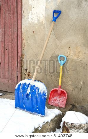 Big And Small Father And Child Snow Shovels Near Wall